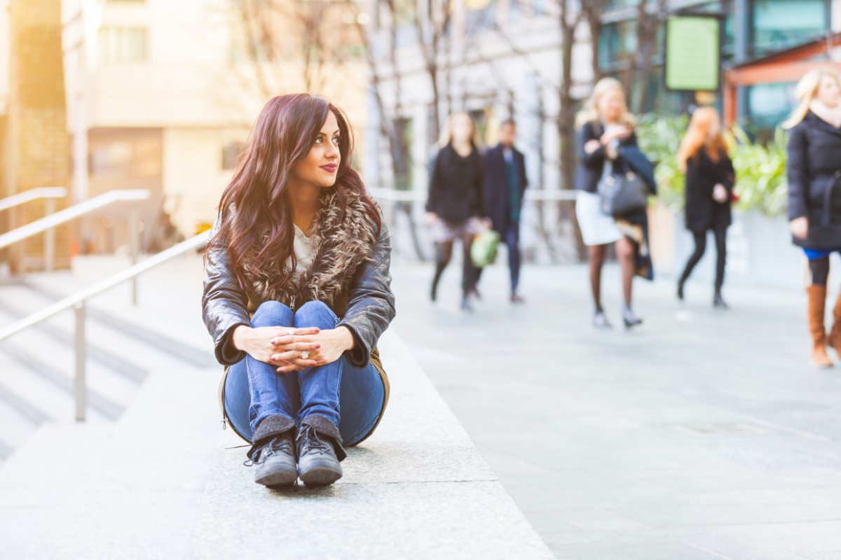 Indian girl portrait in London. She is sitting on a concrete bench with knees pulled up and looking away from camera. On background there are some persons walking on the footpath.