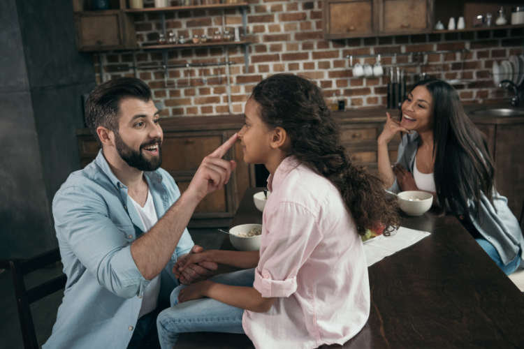 Father in the kitchen with his two daughters. He is putting his finger on the tip of the younger one's nose and laughing.