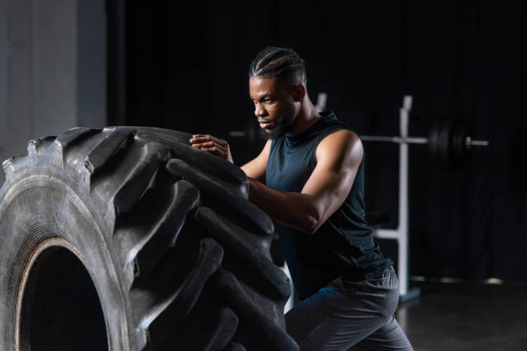 Young adult man working out with a giant truck tire