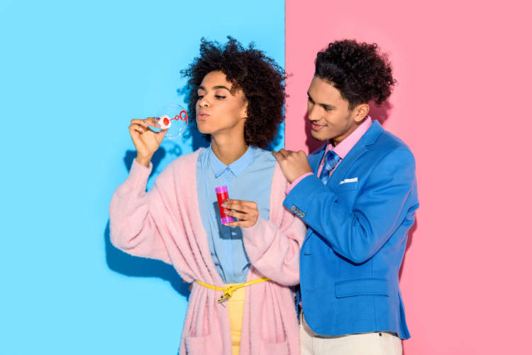 Stylish couple in pink and blue blowing bubbles