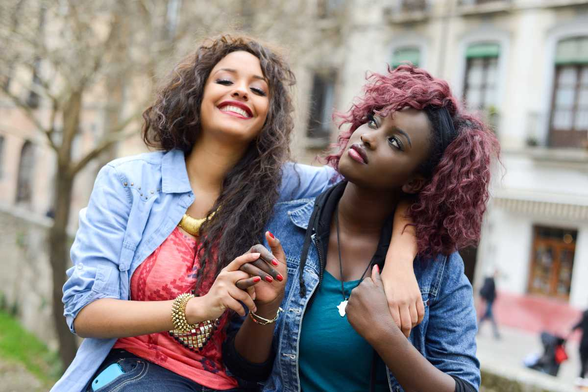 Portrait of two beautiful girls in urban background, black and mixed women. Friends talking