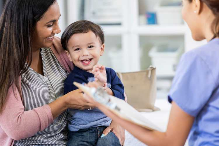 An adorable toddler boy sits in his mother's lap in his unrecognizable pediatrician's office. He smiles and looks away. His pediatrician holds a clipboard.